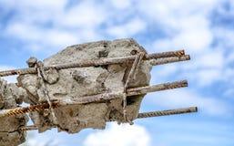 Σκουριασμένες ράβδοι ενός χάλυβα στο σκυρόδεμα Χαλασμένος συγκεκριμένος στυλοβάτης στο μπλε ουρανό Στοκ Εικόνες
