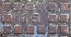 Σκουριασμένη κάλυψη καταπακτών με το ορθογώνιο σχεδιάγραμμα και τον αποτυπωμένο σε ανάγλυφο αριθμό 15 Στοκ εικόνα με δικαίωμα ελεύθερης χρήσης