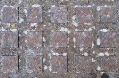 Σκουριασμένη κάλυψη καταπακτών με το τετραγωνικό σχεδιάγραμμα ως υπόβαθρο, σύσταση ή λεπτομέρεια Στοκ Εικόνες