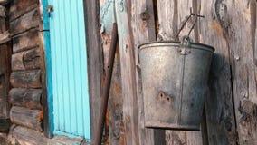 Σκουριασμένος κάδος στον ξύλινο τοίχο μιας παλαιάς σιταποθήκης απόθεμα βίντεο