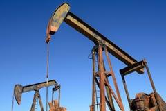 Σκουριασμένο άλογο λικνίσματος Pumpjack πετρελαιοφόρων περιοχών πέρα από μια πηγή Σαφές β Στοκ φωτογραφία με δικαίωμα ελεύθερης χρήσης