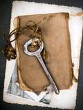 Σκουριασμένο βασικό, παλαιό βιβλίο και κενή φωτογραφία ως μεταφορά μνημών Στοκ Εικόνα