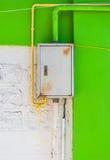 Σκουριασμένο κιβώτιο ελέγχου σιδήρου στον άσπρο και πράσινο συμπαγή τοίχο Στοκ Εικόνες