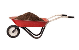 Σκουριασμένο κόκκινο Wheelbarrow με το χώμα Στοκ Φωτογραφίες
