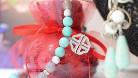 Σκουλαρίκια και ένα περιδέραιο του τυρκουάζ μπλε και άσπρου βάζου σε ένα όμορφο κόκκινο χρώμα απόθεμα βίντεο