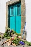 Σκούπα & δέσμες των λουλουδιών που σκορπίζονται στο κατώφλι της τυρκουάζ πόρτας Στοκ εικόνες με δικαίωμα ελεύθερης χρήσης