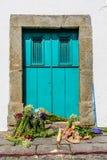 Σκούπα & δέσμες των λουλουδιών που σκορπίζονται στο κατώφλι της τυρκουάζ πόρτας Στοκ Εικόνες