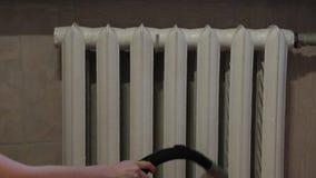 Σκούπισμα με ηλεκτρική σκούπα μεταξύ των τμημάτων ενός θερμαντικού σώματος απόθεμα βίντεο