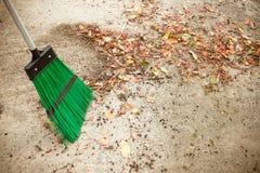 Σκούπισμα των ξηρών φύλλων με τη σκούπα Φθινόπωρο, εποχή πτώσης Σκουπίστε τα φύλλα, άνθρωποι σκουπισμάτων, καθαρίστε τον κήπο Εργ στοκ εικόνα