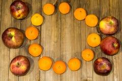 Σκούρο κόκκινο μήλα ενός στα ξύλινα υποβάθρου και κίτρινα tangerines στοκ εικόνα με δικαίωμα ελεύθερης χρήσης