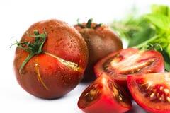 Σκούρο κόκκινο ντομάτα, ολόκληρος και διχοτομημένος στο λευκό στοκ εικόνα με δικαίωμα ελεύθερης χρήσης