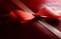 Σκούρο κόκκινο τυλιγμένο παρόν με την κορδέλλα και το τόξο στοκ εικόνες
