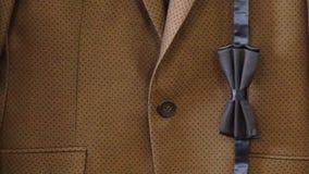 Σκούρο μπλε διαμορφωμένος δεσμός τόξων στο καφετί υπόβαθρο σακακιών κοστουμιών Ευτυχής ημέρα πατέρων ή γαμήλια έννοια φιλμ μικρού μήκους