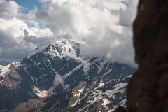 Σκούρο μπλε ουρανός με τα σύννεφα στις δύσκολες αιχμές των βουνών που καλύπτονται με τους παγετώνες και το χιόνι Στοκ Εικόνες