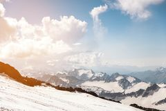 Σκούρο μπλε ουρανός με τα σύννεφα στις δύσκολες αιχμές των βουνών που καλύπτονται με τους παγετώνες και το χιόνι Στοκ εικόνες με δικαίωμα ελεύθερης χρήσης