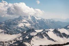 Σκούρο μπλε ουρανός με τα σύννεφα στις δύσκολες αιχμές των βουνών που καλύπτονται με τους παγετώνες και το χιόνι Στοκ Φωτογραφία