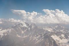 Σκούρο μπλε ουρανός με τα σύννεφα στις δύσκολες αιχμές των βουνών που καλύπτονται με τους παγετώνες και το χιόνι Στοκ φωτογραφία με δικαίωμα ελεύθερης χρήσης
