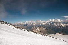 Σκούρο μπλε ουρανός με τα σύννεφα στις δύσκολες αιχμές των βουνών που καλύπτονται με τους παγετώνες και το χιόνι Στοκ Φωτογραφίες
