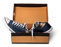 Σκούρο μπλε αθλητικά παπούτσια που εγκαταλείπονται σε ένα κουτί από χαρτόνι Στοκ Εικόνα