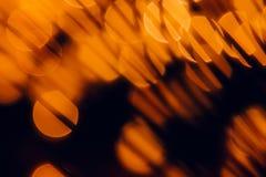 Σκούρο παρτοκαλί κύκλοι Bokeh και χλόες σκιάς στο μαύρο υπόβαθρο Στοκ φωτογραφίες με δικαίωμα ελεύθερης χρήσης