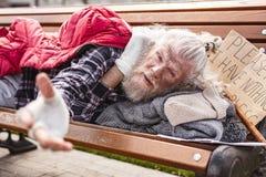 Σκυθρωπός φτωχός άνθρωπος που ζητά τη βοήθεια στοκ εικόνες