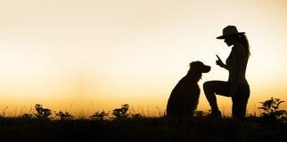 Σκυλί και ο εκπαιδευτής του - εικόνα σκιαγραφιών με το κενό, διάστημα αντιγράφων στοκ φωτογραφίες