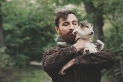 Σκυλί και ο ιδιοκτήτης του - δροσερό σκυλί και νεαρός άνδρας που έχουν τη διασκέδαση σε ένα πάρκο - έννοιες της φιλίας, κατοικίδι Στοκ Εικόνες