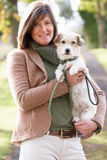 Σκυλί περπατήματος γυναικών υπαίθρια στο πάρκο φθινοπώρου Στοκ φωτογραφία με δικαίωμα ελεύθερης χρήσης