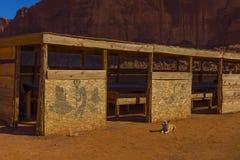 Σκυλί που ξαπλώνει στην κόκκινη γη δίπλα στην καλύβα κοντραπλακέ που διακοσμείται στο ύφος αμερικανών ιθαγενών, Γιούτα στοκ εικόνες