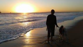 Σκυλί και γεροδεμένος μπροστά από το ηλιοβασίλεμα κοντά στον ωκεανό Στοκ Εικόνες