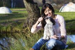 Σκυλί που καλλωπίζεται με τη βούρτσα τρίχας από τη νέα γυναίκα στο πάρκο Στοκ Φωτογραφία