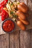 Σκυλιά, τηγανιτές πατάτες, πιπέρι και κέτσαπ καλαμποκιού Κάθετη τοπ άποψη Στοκ Φωτογραφία