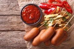 Σκυλιά, τηγανιτές πατάτες, πιπέρι και κέτσαπ καλαμποκιού οριζόντια τοπ άποψη Στοκ Φωτογραφία