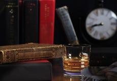 Σκωτσέζικο ουίσκυ τακτοποιημένο με τα βιβλία και το ρολόι στοκ φωτογραφίες