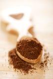 Σκόνη επίγειου καφέ στο ξύλινο κουτάλι μορφής καρδιών Στοκ Εικόνες