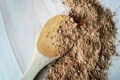 Σκόνη κακάου σωρών που απομονώνεται στο ξύλινο υπόβαθρο Στοκ Εικόνες