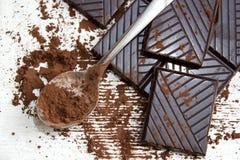 Σκόνη σοκολάτας σε ένα κουτάλι και τα κομμάτια της σκοτεινής σοκολάτας Στοκ εικόνα με δικαίωμα ελεύθερης χρήσης