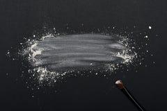 Σκόνη σύνθεσης με τη βούρτσα ομορφιάς στη μαύρη επιφάνεια Στοκ Εικόνες