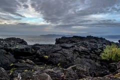 Σκόπελος λάβας στην ακτή και η θάλασσα κάτω από τα σκοτεινά σύννεφα Στοκ Φωτογραφίες
