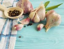 Σκόρδο, μαύρο λαχανικό διατροφής κουζινών φρεσκάδας αρώματος καρυκευμάτων πιπεριών εκλεκτής ποιότητας στο μπλε ξύλο Στοκ φωτογραφίες με δικαίωμα ελεύθερης χρήσης