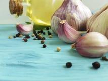 σκόρδο, μαύρο λαχανικό διατροφής κουζινών φρεσκάδας καρυκευμάτων πετρελαίου μπουκαλιών πιπεριών στο μπλε ξύλο Στοκ Φωτογραφία