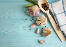 Σκόρδο, μαύρο λαχανικό διατροφής κουζινών φρεσκάδας καρυκευμάτων πιπεριών εκλεκτής ποιότητας στο μπλε ξύλο Στοκ Εικόνες