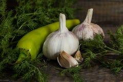 Σκόρδο, πράσινο καυτό πιπέρι με τον άνηθο σε έναν ξύλινο πίνακα στοκ εικόνες