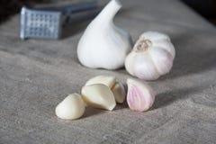 Σκόρδο Βολβοί σκόρδου με τα γαρίφαλα burlap στο υπόβαθρο, υγιής τρόπος ζωής έννοιας Στοκ Εικόνα