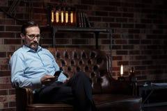 Σκληρά εργαζόμενος ήρεμος επιχειρηματίας που εξετάζει το τηλέφωνο κυττάρων Στοκ φωτογραφία με δικαίωμα ελεύθερης χρήσης