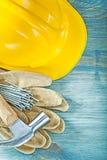 Σκληρά καρφιά σφυριών νυχιών γαντιών ασφάλειας δέρματος καπέλων στον ξύλινο πίνακα γ Στοκ Φωτογραφία