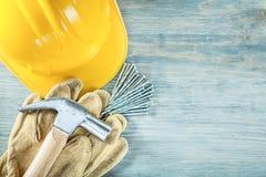 Σκληρά καρφιά σφυριών νυχιών γαντιών ασφάλειας καπέλων στο ξύλινο constru πινάκων Στοκ Φωτογραφία