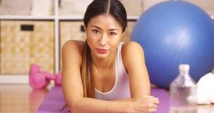 Σκληρή ιαπωνική γυναίκα που στηρίζεται μετά από το workout στοκ φωτογραφία