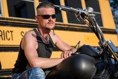 Σκληρός άνδρας με τα γυαλιά ήλιων που στη μοτοσικλέτα μπαλτάδων του Στοκ Φωτογραφίες
