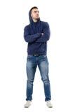 Σκληρός βέβαιος νεαρός άνδρας με το hoodie στα επικεφαλής και διασχισμένα όπλα που ανατρέχει Στοκ Εικόνες